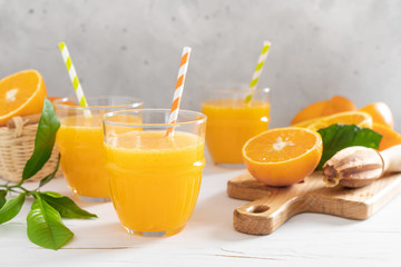 Photo sur Plexiglas Jus, Sirop Orange juice. Freshly squeezed juice in glasses and fresh fruits with leaves