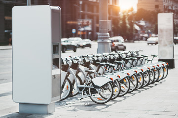 Modern rental electric bikes standing a row during charging on a bright day with a selective focus on the vertical payment terminal with a mock-up of informational or an ad banner placeholder on it