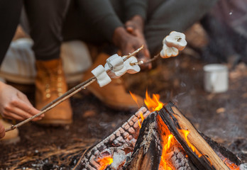 Close up of travellers frying marshmallow in forest