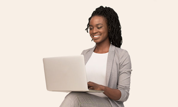 African American Girl Working On Laptop Sitting Over White Background