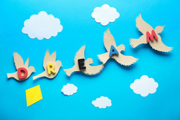 Papiers peints Oiseau Paper birds with word DREAM and clouds on color background