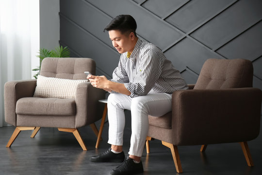 Asian man with mobile phone at home