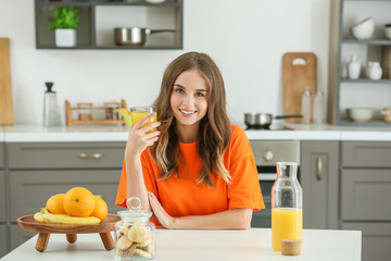 Beautiful young woman drinking orange juice in kitchen