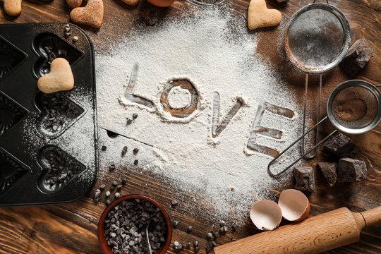 Word LOVE written on flour, top view