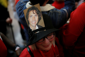 A supporter of Liberal leader and Canadian Prime Minister Justin Trudeau wears a hat with a picture of Trudeau stuck to it during a rally in Winnipeg