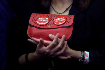 A supporter of Liberal leader and Canadian Prime Minister Justin Trudeau holds her handbag with badges on it during a rally in Winnipeg, Manitoba