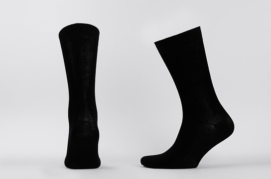 Blank black cotton high socks on invisible mannequin foot as mock up for advertising, branding, design. Back and side view, sportwear template on white background.