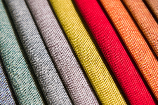 Colorful and bright fabric samples of furniture and clothing upholstery. Close-up of a palette of textile abstract diagonal stripes of different colors