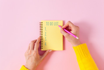 To do list in spiral notepad. Pink background, flat lay style..