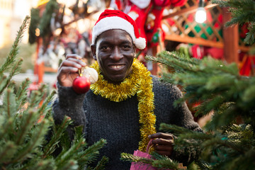 Cheerful man choosing Christmas tree