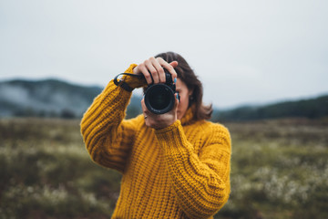 photographer tourist take photo on camera lens on background autumn foggy mountain, traveler hipster shooting video nature mist landscape, hobby vacation concept, copy space