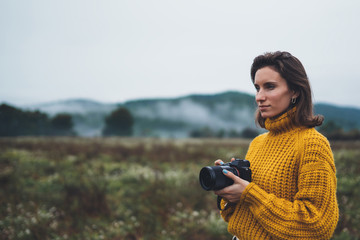 Wall Mural - photographer tourist take photo on camera lens on background autumn foggy mountain, traveler hipster shooting video nature mist landscape, hobby vacation concept, copy space