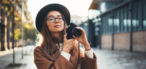 Hobby photographer concept. Outdoor lifestyle portrait of pretty young woman in sun city in Europe with camera travel photo of photographer in glasses and hat take photo copy space mockup