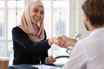 Happy asian muslim hr handshake male applicant at interview meeting