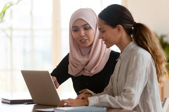 Asian muslim female mentor teaching caucasian intern explaining computer work