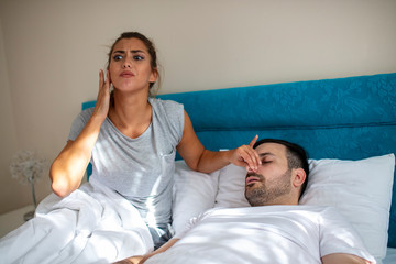 Snoring man. Couple in bed, man snoring and woman can not sleep. Picture of angry woman in bed with snoring man. Portrait of woman blocking ears with hands while man snoring on bed