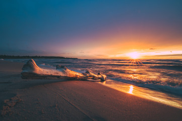 Colorful sunset at sandy beach. Gentle waves in the sea glance the coastline. Peaceful scene with warm sunrays in background.