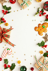 Christmas background with gingerbread cookies, gift boxes and branches of holly with red berries on...