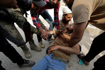 Wounded man is helped in the town of Tal Abyad