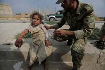 Wounded girl cries as she is helped by a Turkey-backed Syrian rebel fighter in the town of Tal Abyad