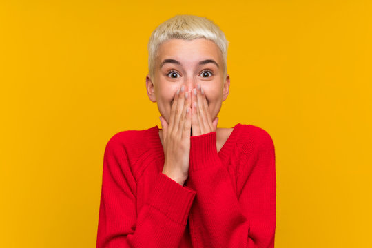 Teenager girl with white short hair over yellow wall with surprise facial expression