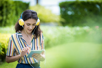 Portrait of a beautiful woman has listening to music with smiling and relax in the garden.