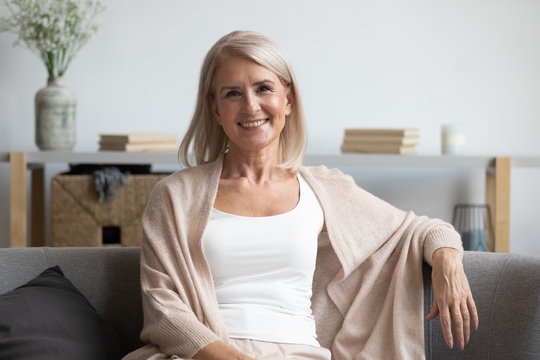Happy middle aged woman looking at camera at home
