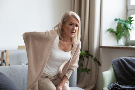 Worried upset mature woman feel hurt sudden back ache