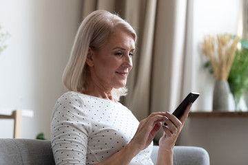 Happy middle aged woman using mobile apps texting at home