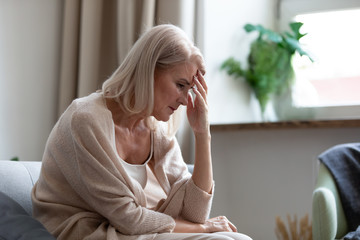 Sad mature woman sitting alone at home feeling headache depression