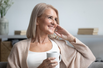 Happy dreamy old woman relaxing at home drinking coffee Wall mural