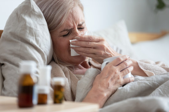 Ill middle aged woman sneezing blowing nose sit on bed