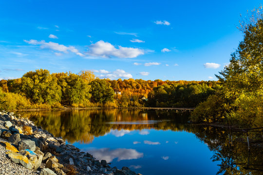 autumn landscape with blue sky and a small lake