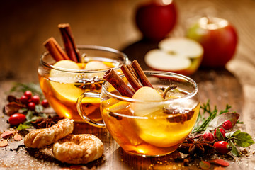 Mulled cider with apple slices, cinnamon sticks, cloves, anise stars and citrus fruits in glass cups on a wooden rustic table. Delicious, traditional hot drink Fototapete