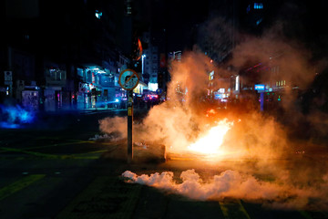 A cloud of tear gas is seen near a burning barrier as riot police try to disperse anti-government protesters at Mong Kok in Hong Kong