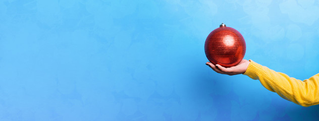 christmas red ball on hand over blue background, merry christmas concept, panoramic mock up image