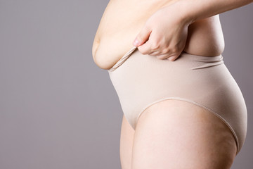 Fat woman in corrective panties, flabby belly after pregnancy, overweight female body on gray background