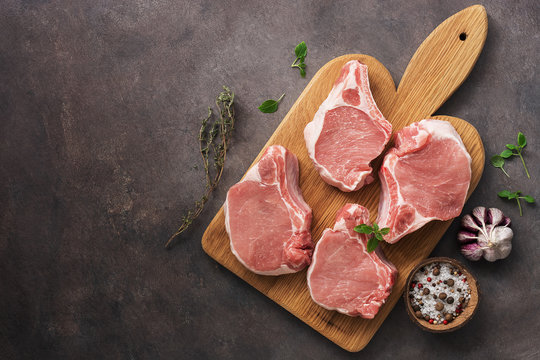 Raw pork slices on a cutting board with spices and herbs, dark rustic background. Top view, flat lay, copy space.