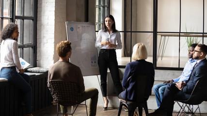 Obraz Confident lady business trainer coach give flip chart presentation - fototapety do salonu