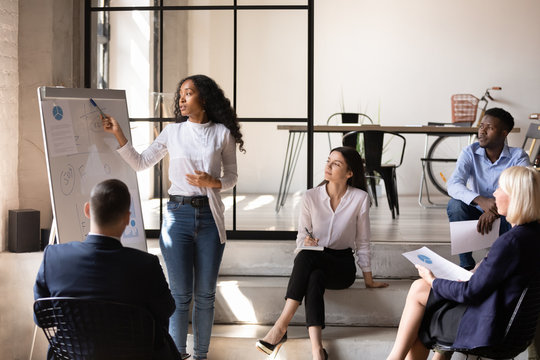 African businesswoman manager give presentation on whiteboard at office meeting