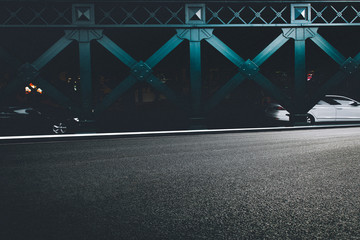 Clean asphalt road beside steel girder bridge