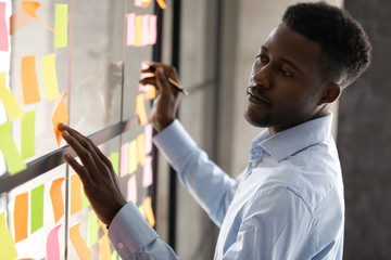 Serious african american businessmen managing project tasks on sticky notes