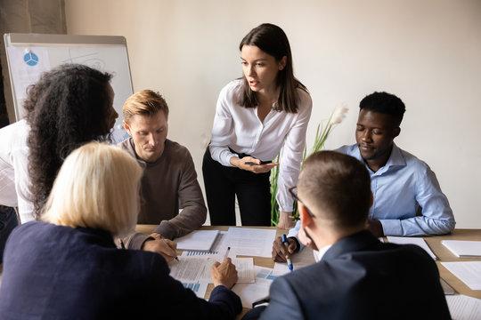 Female mentor teaching diverse employees group analyze paperwork at briefing