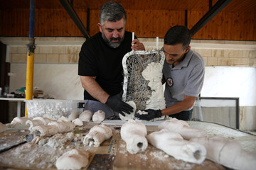 A worker helps Omar Sartawi, a Jordanian chef, as he recreates an ancient statue found in Jordan using a famous local product - Jameed, at his workshop in Amman