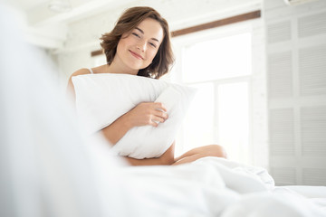 Cute young happy female hugging her pillow
