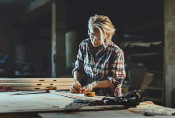 Attractive middle aged woman carpenter designer works with ruler, make notches on the tree in workshop.  Image of modern femininity. Concept of professionally motivated women