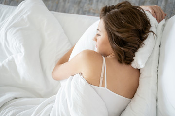 Serene Caucasian young woman sleeping in bed