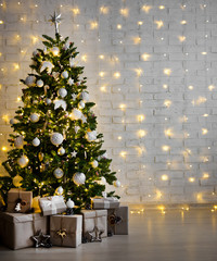decorated christmas tree with white balls, garlands and gift boxes over white brick wall