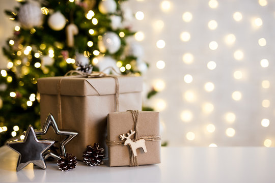 christmas and new year background - gift boxes and stars near decorated christmas tree and copy space over white wall with lights