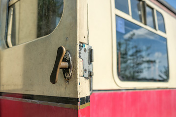 Close-up view of the old slam-door passenger train door handle, seen in the opened position, on a first class passenger train car.